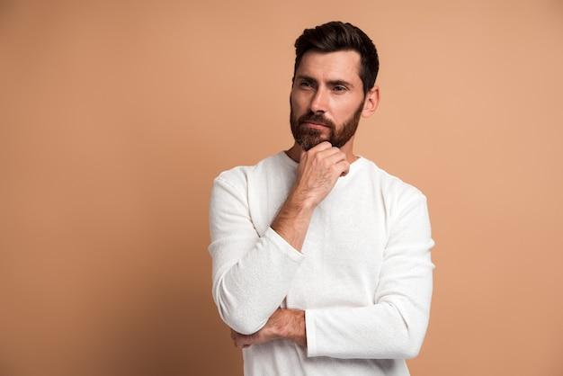 Portrait d'un beau jeune homme barbu pensif debout, touchant son visage, regardant de côté et pensant à quelque chose. prise de vue en studio intérieur, isolé sur fond beige