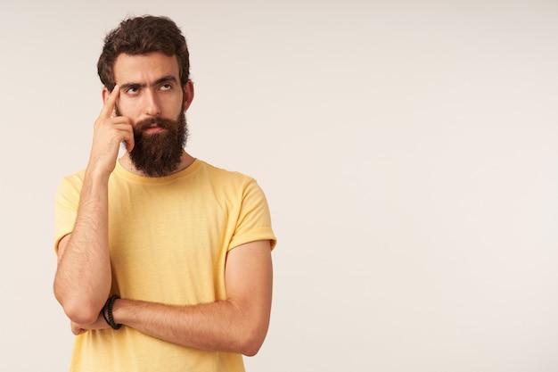 Portrait de beau jeune homme barbu regardant de côté debout à droite contre le mur blanc bras toucher barbe émotion sceptique douteur penseur