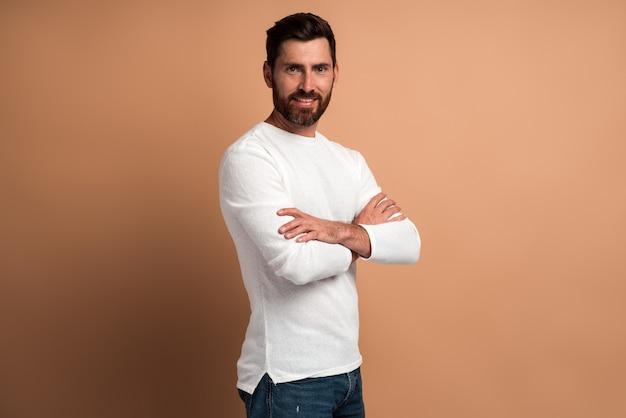 Portrait de beau jeune homme barbu satisfait en chemise blanche debout avec les bras croisés et regardant la caméra avec le sourire. studio intérieur tourné isolé sur fond beige