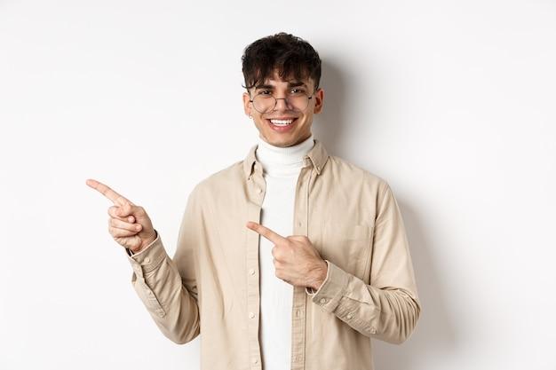 Portrait d'un beau jeune homme caucasien dans des verres montrant le logo, souriant et pointant du doigt vers la gauche, invitant à consulter l'offre promotionnelle, fond blanc.