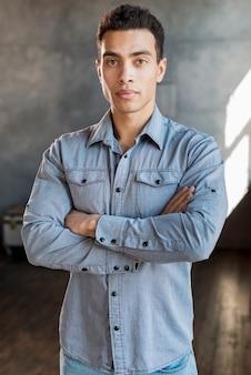 Portrait d'un beau jeune homme en chemise en jean avec les bras croisés en regardant la caméra