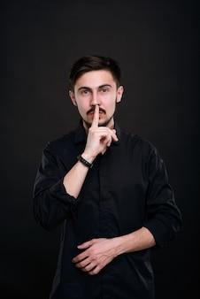 Portrait de beau jeune homme en chemise noire tenant l'index près de la bouche tout en demandant de garder le silence