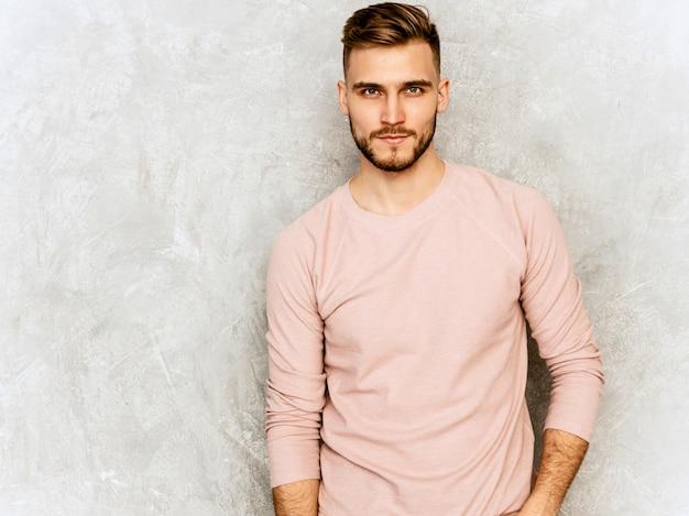 Portrait de beau jeune homme confiant modèle portant des vêtements décontractés d'été rose. homme élégant de mode posant. lumière du jour