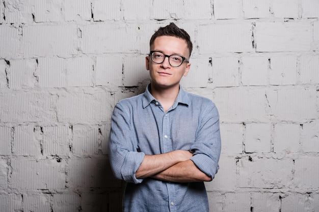 Portrait, de, beau, jeune homme, dans, jean, vêtements, et, lunettes, regarder appareil-photo, sourire, debout, contre, mur brique grise
