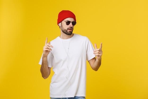 Portrait d'un beau jeune homme dansant et écoutant de la musique, isolé sur l'espace jaune