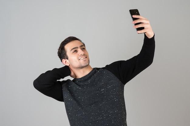 Portrait de beau jeune homme debout et prenant selfie sur mur gris