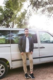 Portrait d'un beau jeune homme devant la voiture