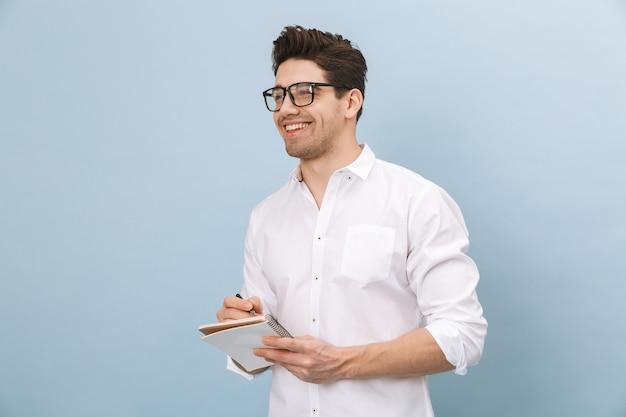 Portrait d'un beau jeune homme gai portant des lunettes debout isolé sur bleu, en prenant des notes