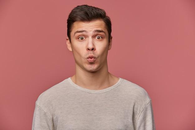 Portrait de beau jeune homme gai porte en blanc à manches longues, regarde la caméra avec des expressions heureuses, sens baiser, se dresse sur fond rose.