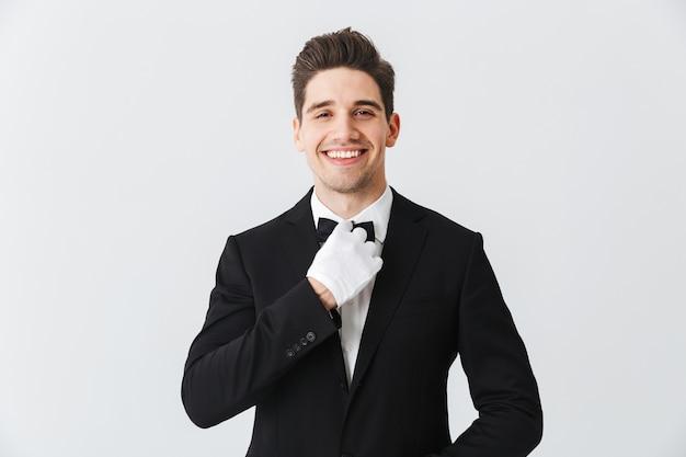 Portrait d'un beau jeune homme garçon portant smoking et gants debout isolé sur mur blanc