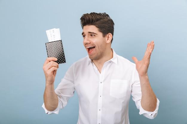 Portrait d'un beau jeune homme joyeux debout isolé sur bleu, tenant un passeport avec des billets d'avion