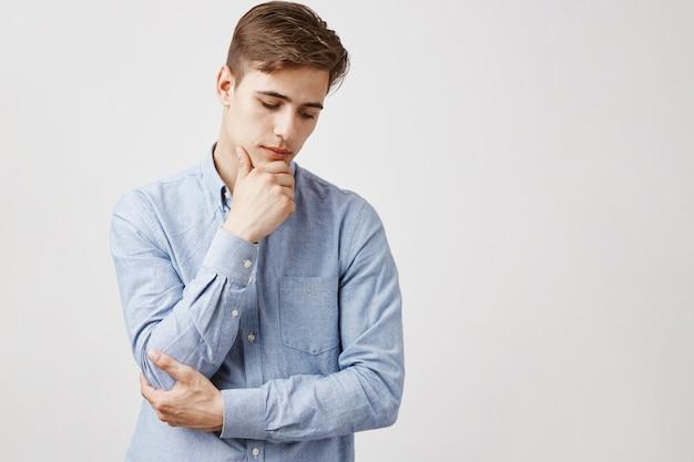 Portrait de beau jeune homme avec la main sur le menton, regard réfléchi