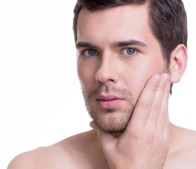 Portrait de beau jeune homme avec la main près du visage sur un mur blanc.