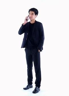 Portrait de beau jeune homme parlant au téléphone sur blanc