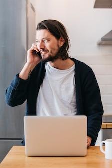 Portrait, beau, jeune homme, parler téléphone portable, à, ordinateur portable, sur, table