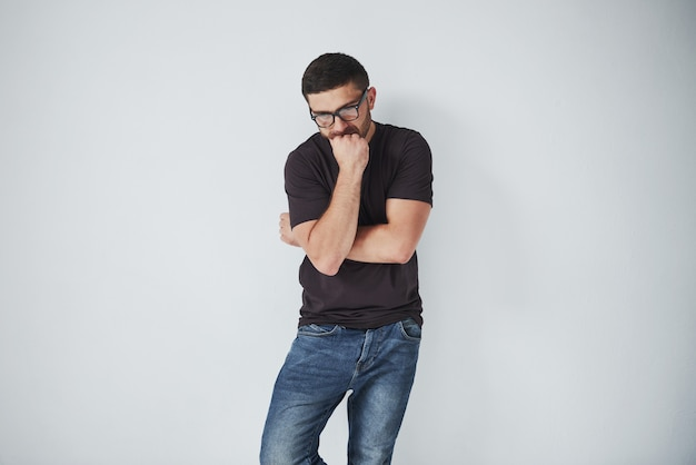 Portrait d'un beau jeune homme pensant à quelque chose, isolé sur blanc