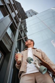 Portrait d'un beau jeune homme portant des lunettes de soleil vue de dessous tenant une tasse de café cappuccino à emporter debout sur un bâtiment en verre de la rue urbaine skateur hipster tenant un longboard.