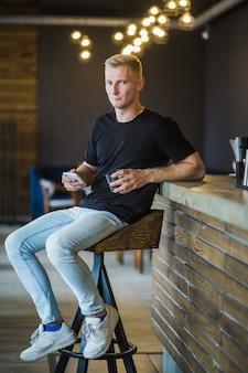 Portrait, de, beau, jeune homme, séance, sur, tabouret bar, tenue, boisson, et, smartphone
