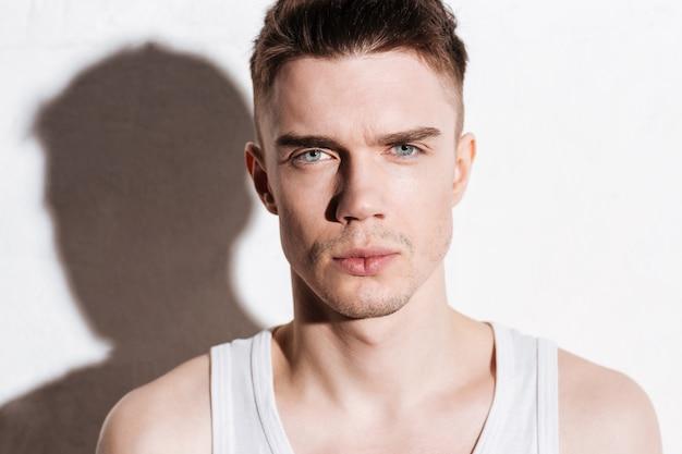 Portrait de beau jeune homme sérieux aux yeux bleus