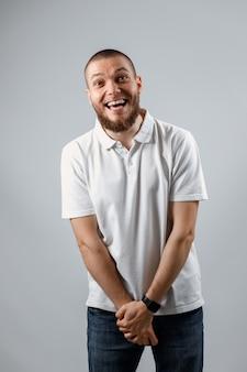 Portrait d'un beau jeune homme timide dans un t-shirt blanc sur gris