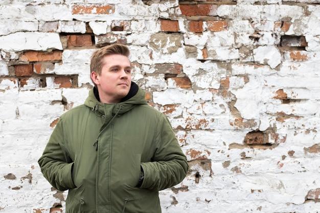 Portrait de beau jeune homme en veste, debout contre le vieux mur de briques blanches et rouges, l'heure d'hiver