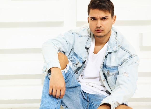 Portrait de beau jeune mannequin homme habillé en jeans assis près d'un mur texturé blanc