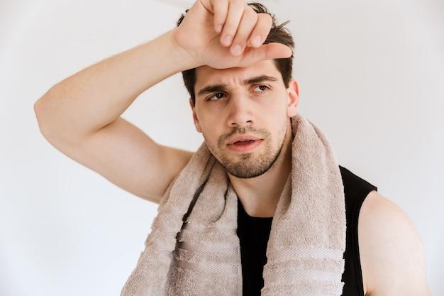 Portrait d'un beau jeune sportif fatigué isolé sur un mur blanc tenant une serviette.