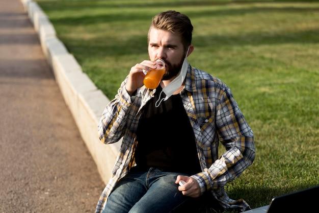 Portrait de beau mâle boire du jus