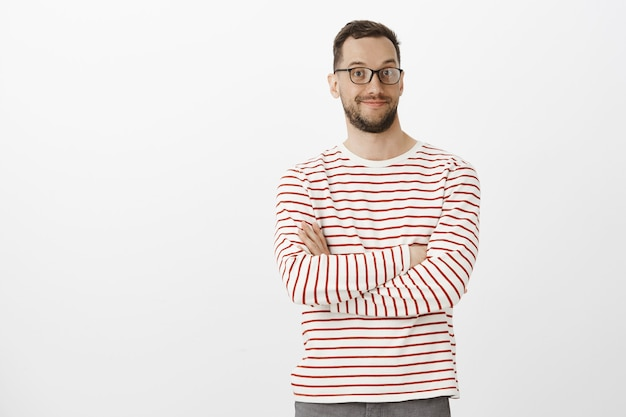 Portrait de beau mâle intrigué agréable à lunettes noires, souriant largement