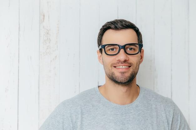 Portrait de beau mâle mal rasé aux cheveux noirs, porte des lunettes, a un doux sourire, regarde directement dans la caméra