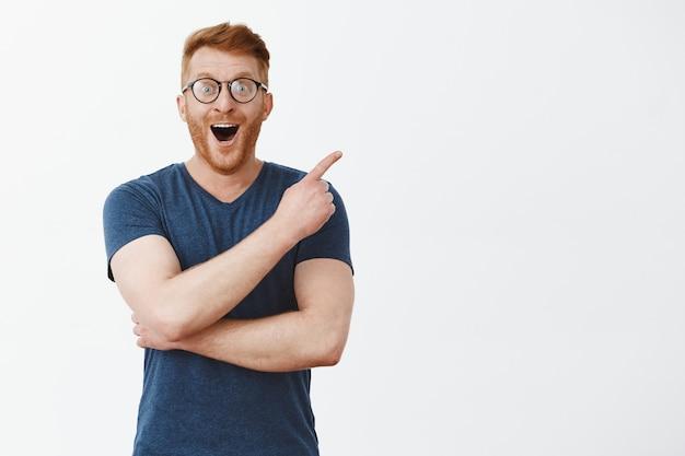 Portrait de beau mâle rousse européenne avec poils dans des verres et t-shirt, souriant joyeusement, pointant vers le coin supérieur droit