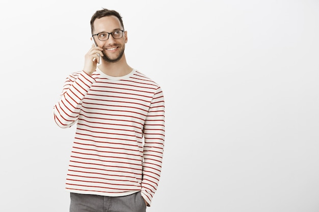 Portrait de beau mâle sympathique dans des lunettes à la mode et une tenue décontractée, regardant tout en appelant un ami via smartphone