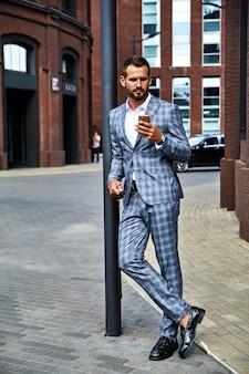 Portrait de beau mannequin d'affaires vêtu d'un élégant costume à carreaux