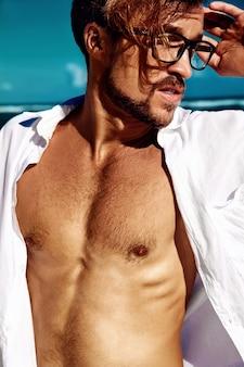 Portrait de beau mannequin bain de soleil mannequin portant des vêtements de chemise blanche dans des verres posant sur ciel bleu
