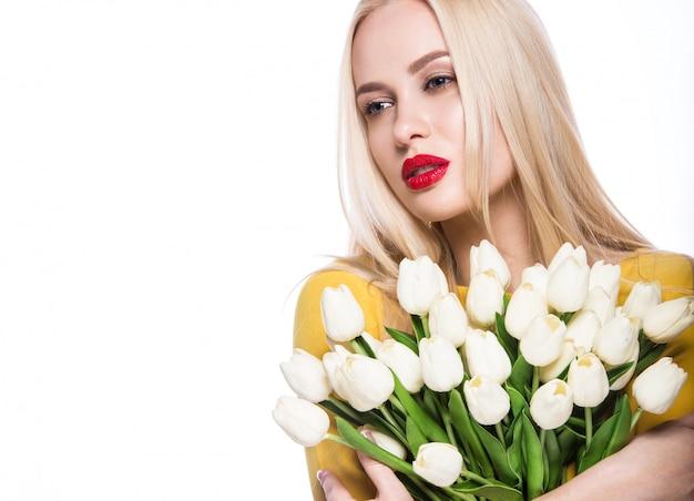 Portrait de beau mannequin avec bouquet de lys dans les mains