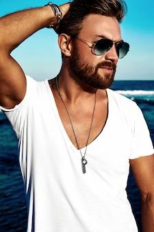 Portrait de beau mannequin portant des vêtements blancs posant sur la mer bleue