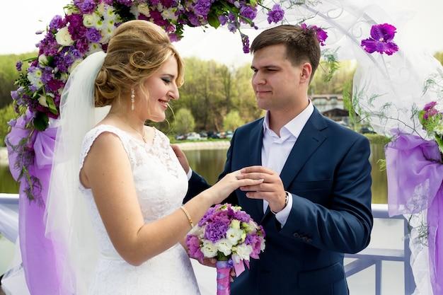Portrait de beau marié souriant mettant l'anneau sur la main de la mariée