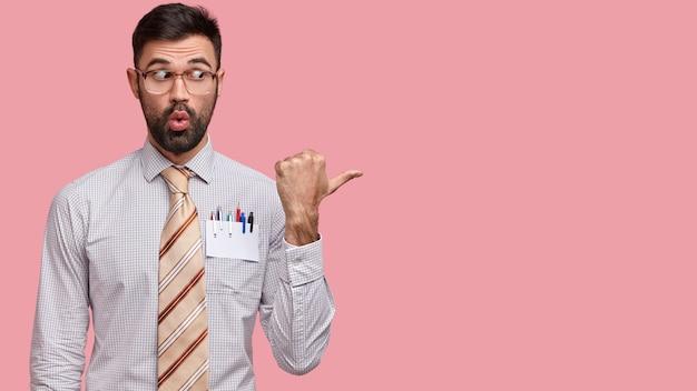 Portrait de beau mec barbu dans des vêtements formels, regarde avec étonnement de côté, pointe un espace vide