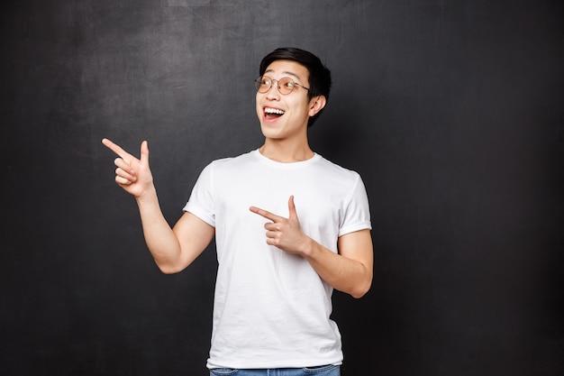 Portrait de beau mec chinois enthousiaste et excité en chemise blanche, bouche ouverte amusé à la recherche et pointant le coin supérieur gauche sur, repérer de grandes remises