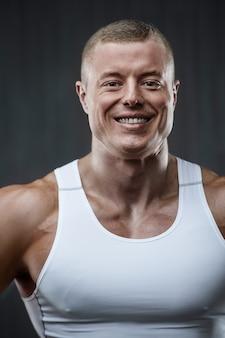 Portrait d'un beau mec dans la salle de gym