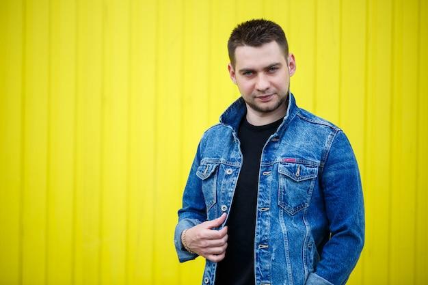 Portrait d'un beau mec élégant, un homme vêtu d'un t-shirt blanc noir debout sur un fond de mur jaune. style urbain de vêtements, image à la mode moderne. la mode masculine