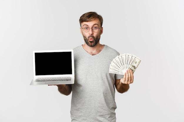 Portrait de beau mec étonné montrant écran d'ordinateur portable et tenant de l'argent