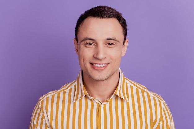 Portrait de beau mec gai positif à pleines dents sourire rayonnant sur fond violet