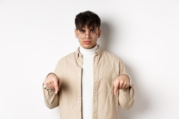 Portrait de beau mec hipster dans des verres montrant une annonce, pointant du doigt le logo, debout sur fond blanc.