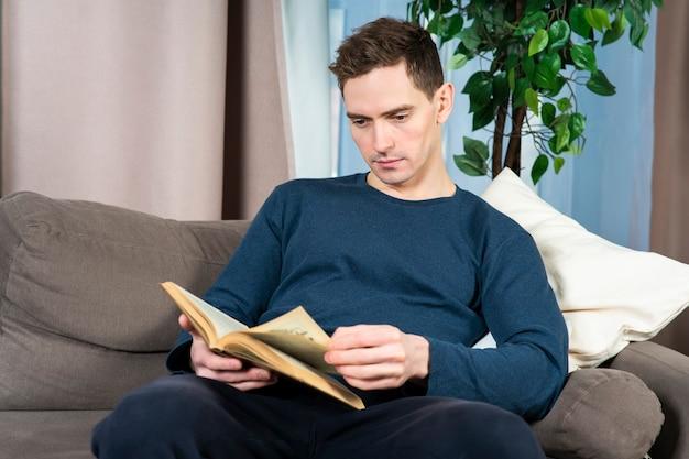 Portrait de beau mec intelligent, jeune homme sérieux attrayant, lisant un livre intéressant à