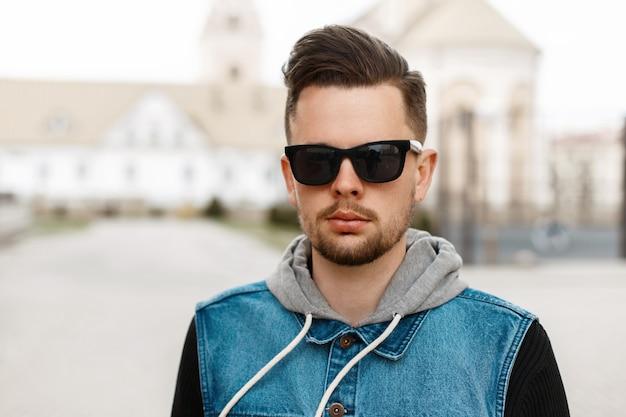 Portrait d'un beau mec à lunettes de soleil et une veste en jean dans la ville