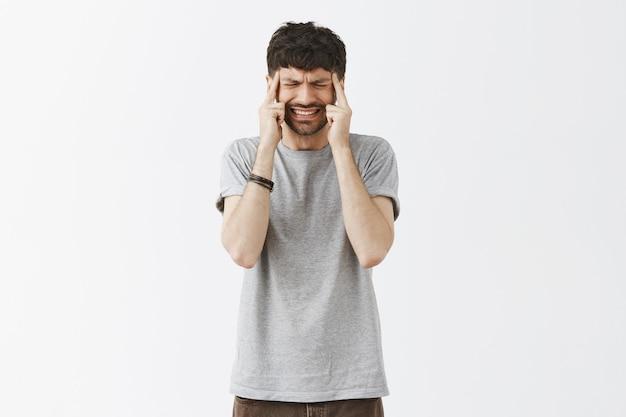 Portrait de beau mec posant contre le mur blanc