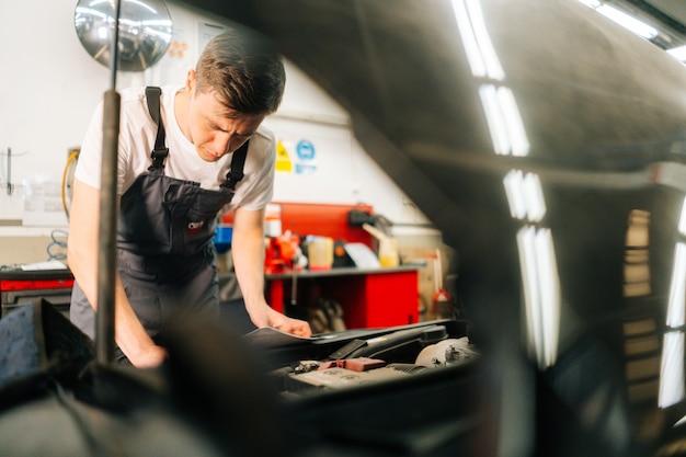Portrait d'un beau mécanicien automobile professionnel concentré en uniforme bleu, debout devant l'op...