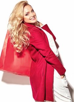 Portrait, de, beau, mignon, heureux, doux, surpris, femme blonde, girl, tenue, dans, elle, mains, grand, sac à provisions, dans, hipster, vêtements rouges, isolé, blanc