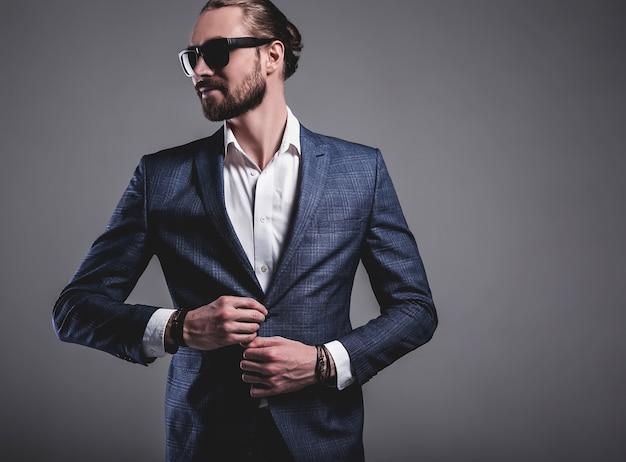 Portrait, de, beau, mode, élégant, hipster, homme affaires, modèle, habillé, dans, élégant, costume bleu, dans, lunettes soleil, poser, sur, gris
